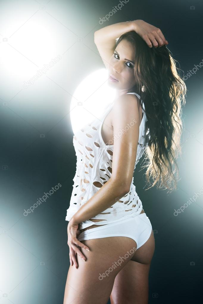 Sexy woman dressed in ripped white shirt and panties from behind — Stock Photo #13736878