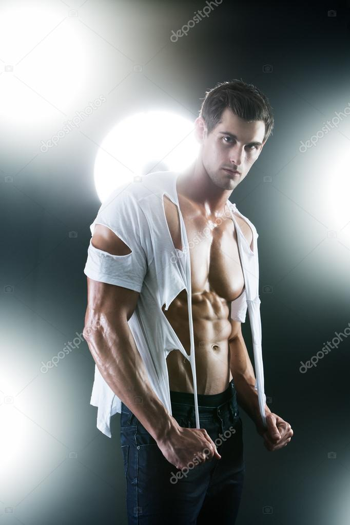 Sexy muscular male in white ripped shirt in studio — Stock Photo #13736890
