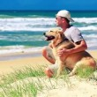 Male owner sitting on a beach with a dog - Stock Photo