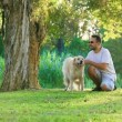 Dog and his owner in the park together - Stock Photo