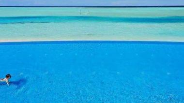 Jovem mulher a nadar na piscina de beiral infinito nos trópicos — Vídeo Stock