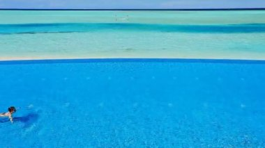 Junge frau schwimmen über infinity-pool in tropen — Stockvideo