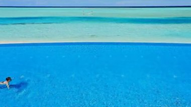 Jeune femme natation dans la piscine à débordement dans les tropiques — Vidéo