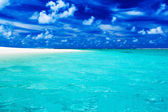 Deserted tropical beach with clear blue water and cloudy sky — Stock Photo