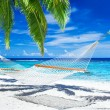 Hammock between palm trees on tropical beach — Stock Photo #45350469