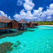 Over water bungalows with steps into green coral lagoon — Stock Photo