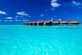 Overwater villas in blue tropical lagoon — Stock Photo