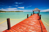 Wooden red jetty extending to tropical lagoon — Stock Photo