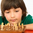 Boy thinking a chess game isolated on white background — Stock Photo