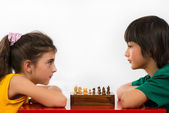 Two children playing chess isolated on white background — Stock Photo
