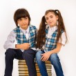 Royalty-Free Stock Photo: Beautiful girl and a boy sitting on a pile of books