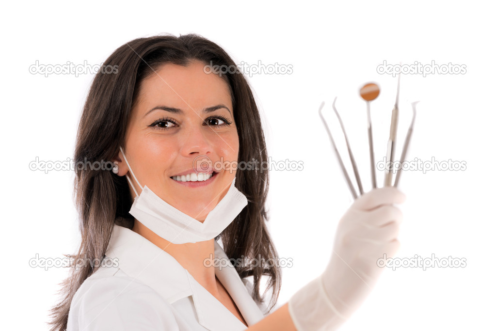 A young dentist with a tool on a white background  Stock Photo #15605261