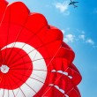 Parachute and airplane on blue sky — Stock Photo