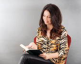 Young woman sitting on a chair reading a book — Foto de Stock