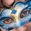 Stock Photo: Womwith blue eyes wearing feathered Venetimask