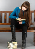 Beautiful young woman sitting on a bench and reading a book — Stock Photo