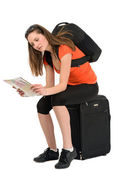 A beautiful woman tourist with a map in hand luggage isolated on — Stock Photo