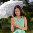Young beautiful womwith umbrellin park — Stock Photo #27068867