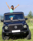 Happy young woman getting out the car's sunroof — Stock Photo