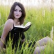 The girl sitting on a grass, reading a book — Stockfoto