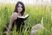 The girl sitting on a grass, reading a book — Stock Photo