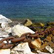 Stock Photo: Metal chain secures distant ship to shore.