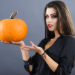 Beautiful girl with pumpkin in the studio isolated on gray backg — Stock Photo