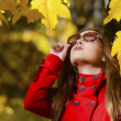 Beautiful young girl looking up on autumn background — Stock Photo