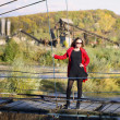 Beautiful blond woman posing on the suspension bridge on a autumn sunny bright day — ストック写真