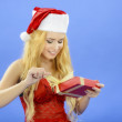 Christmas woman holding gift wearing Santa hat. Isolated on blue — Stock Photo