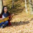 Beautiful brunette guitar player girl in the forest — Stock Photo