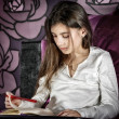 Cute Little girl writing on a notebook lying on her bed — Stock Photo #40586999