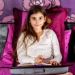 Cute Little girl writing on a notebook lying on her bed — Stock Photo #40587011
