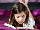 Leisure reading girl is comfortable lying on her bed with a book — Stock Photo