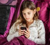Vacker ung kvinna med mobilen i sängen — Stockfoto