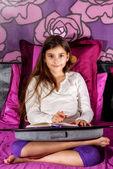 Roztomilá holčička psaní na notebooku, ležící na posteli — Stock fotografie