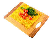 Pasta , tomatoes and dill on a wooden background — Stock Photo