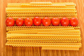 Italian pasta spaghetti and cherry tomato isolated on wooden bac — Foto de Stock