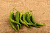 Green hot chili peppers background burlap — Stock Photo