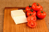 Cheese and tomatoes on a cutting board — Stock Photo