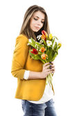 Young woman with tulips isolated on a white background — Stock Photo