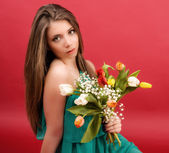 Beautiful girl in a summer dress with tulips on a red background — Stock Photo