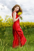 Beautiful young  woman in red dress in yellow field — Stock Photo