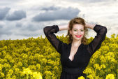 Beautiful young  woman in black dress in yellow field — Stock Photo
