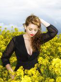 Beautiful young  woman in black dress in yellow field — Stock Photo