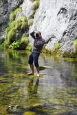 Professional photographer standing in water to make the picture — Zdjęcie stockowe