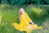 Beautiful woman in yellow dress posing in nature — Stock Photo