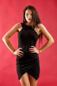 Sexy brunette woman in black dress isolated on red background — Stock Photo