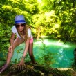 Tourist woman walking through the woods along a river — Stock Photo #50882357