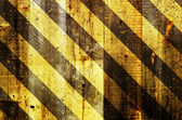 Under construction strips on wooden background — Stock Photo